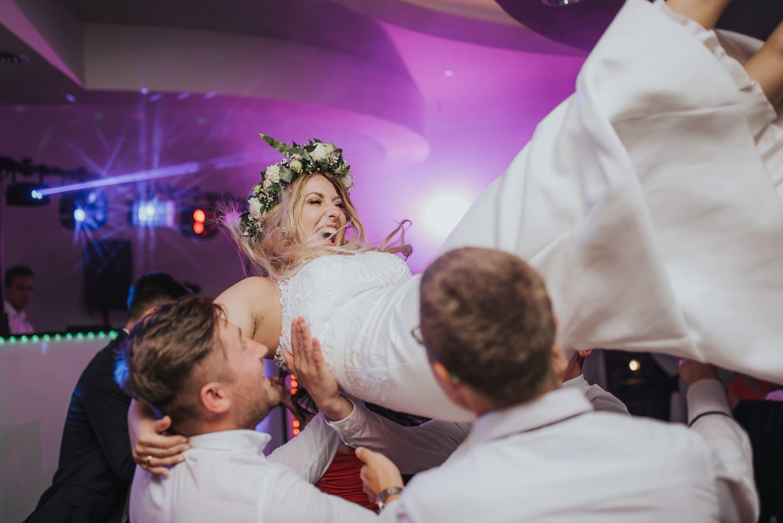 Panna Młoda podrzucana przez gości na weselu, Panna Młoda z prostej sukience, Panna Młoda z wiankiem na głowie